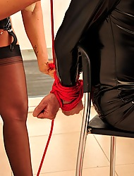 Lucy Zara wearing a airless red bootlace and having some chain play around a gimp
